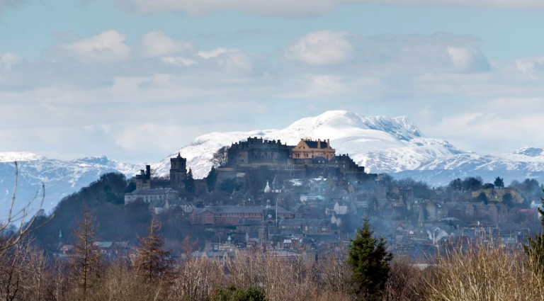Stirling Castle flanked by snowcapped mountains