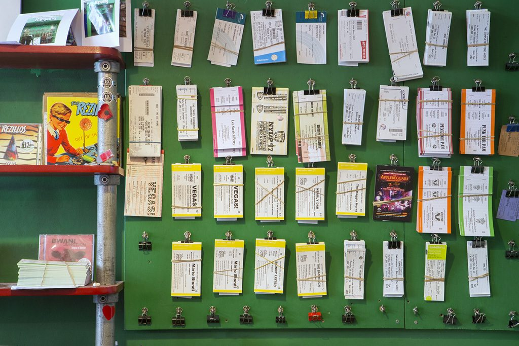 Tickets ready for collection on the wall of a record shop.
