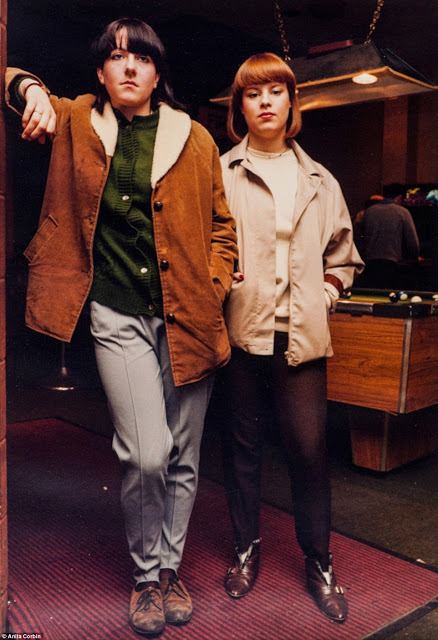 A photo from the Visible Girls exhibition showing two young women posing in front of a bar's pool table.