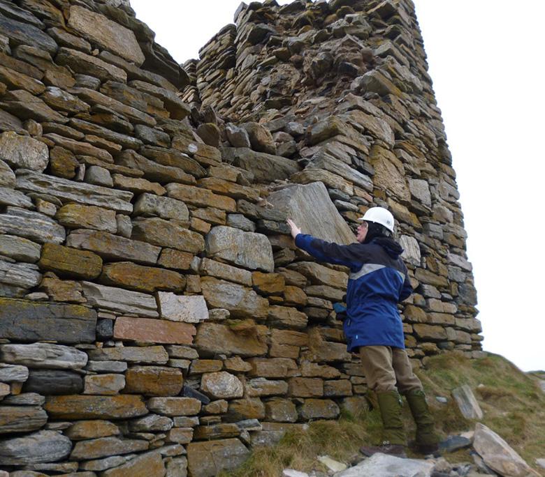 A man in a hard hat examines the wall of Caisteal Bharraich