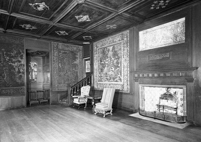 Interior of an ornate wood-panelled room with a large fireplace and tapestries on the walls.