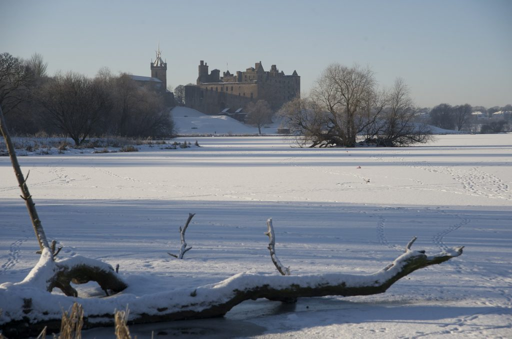 A view of Linlithgow Palace across a snow covered Linlithgow Peel