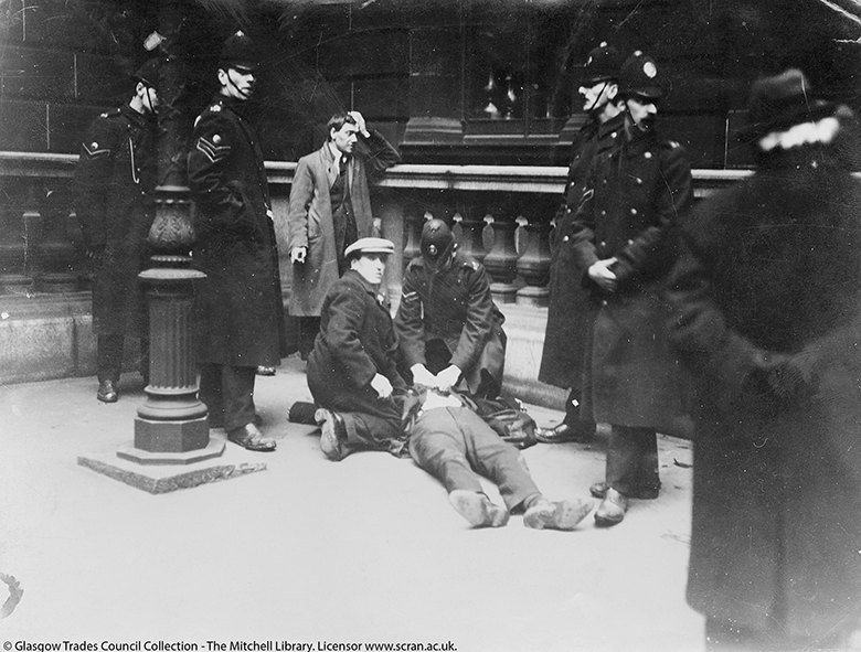 A man lying beside a lampost in George Square, having been struck down. He is surrounded by uniformed policemen.