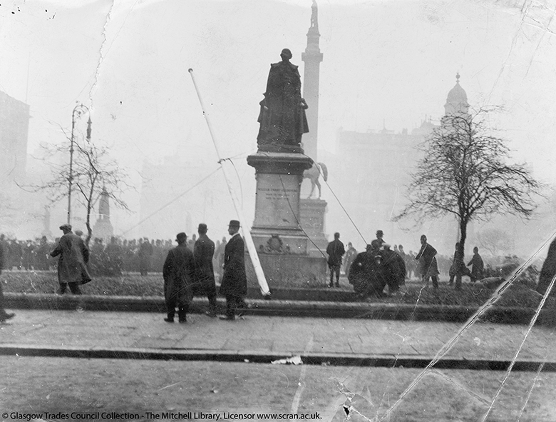An old, damaged photograph showing a large gathering of men in George Square. Statues and wintry trees loom over them.