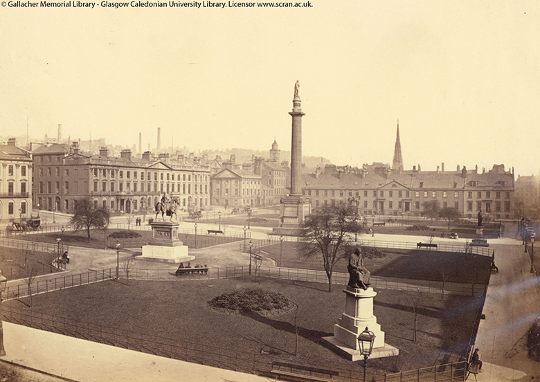 An archive photograph showing an ornate square flanked by large municipal buildings. Statues and a large column can be seen in the gardens in the centre.