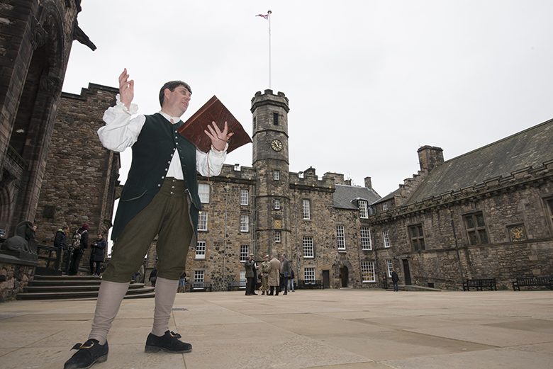 A man dressed as Rabbie Burns stands in front of Edinburgh Castle with a book of poetry in his hand