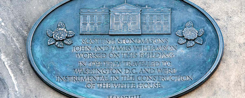Close-up shot of a blue commemorative plaque featuring an engraving of the White House.