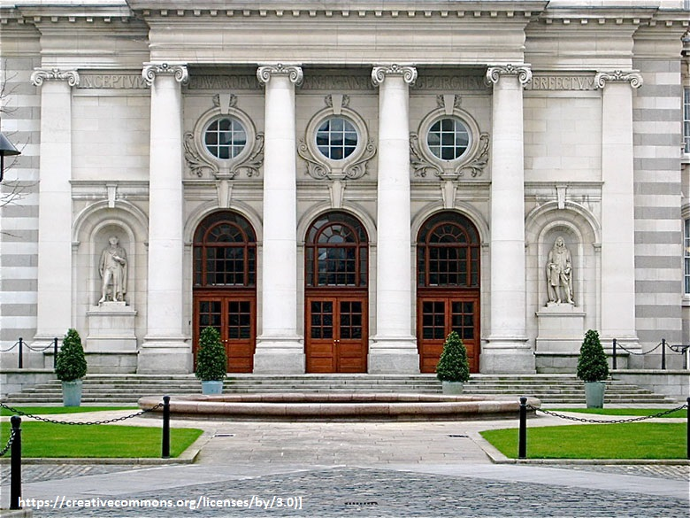 The doorway to Leinster House. Three arched doors are flanked by grand columns. A circular window is above each door and carved stone figures can be seen on either side.