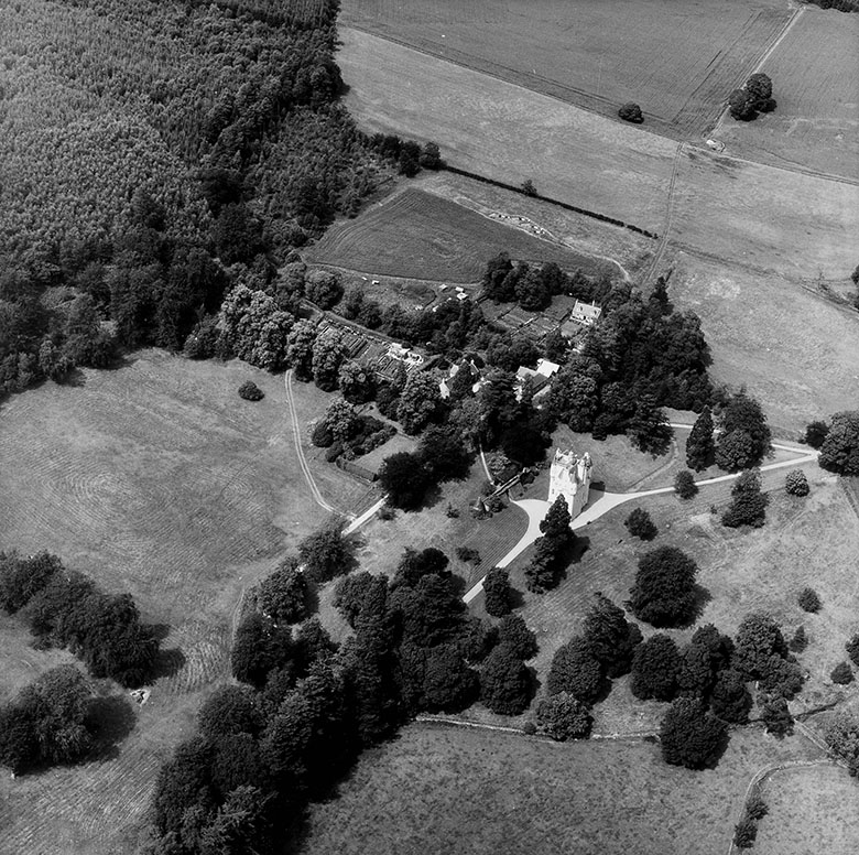 Black and white aerial shot of a tower house surrounded by forest and farmland