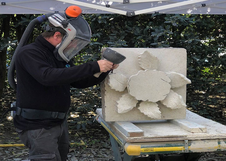 Photo of a HES stonemason wearing protective headgear and working on a carving of a rose.