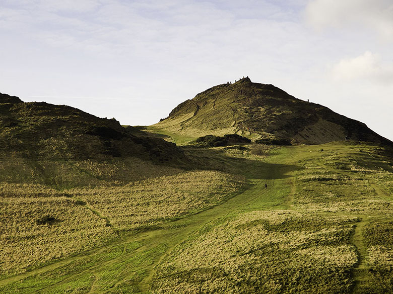 A modern view of Arthur's Seat, Edinburgh with some climbers on the summit.