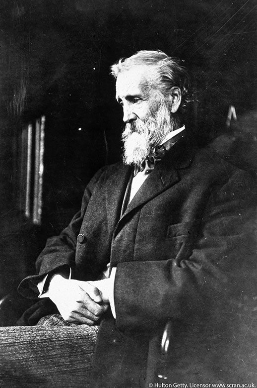 A photo of John Muir in a black suit. He has white hair and a long white beard.