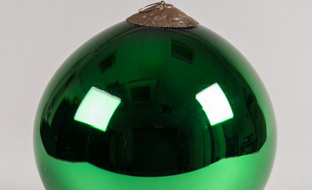 a large, green, lustrous ball. It looks a lot like a large Christmas bauble.
