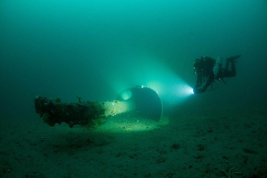 A diver beneath the water exploring marine wreckage with a torch