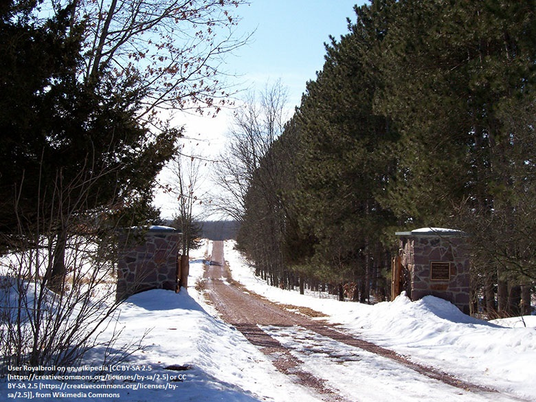 Photo showing the gated entrance to a farm. The farm track is flanked by tall trees and snow is on the ground.