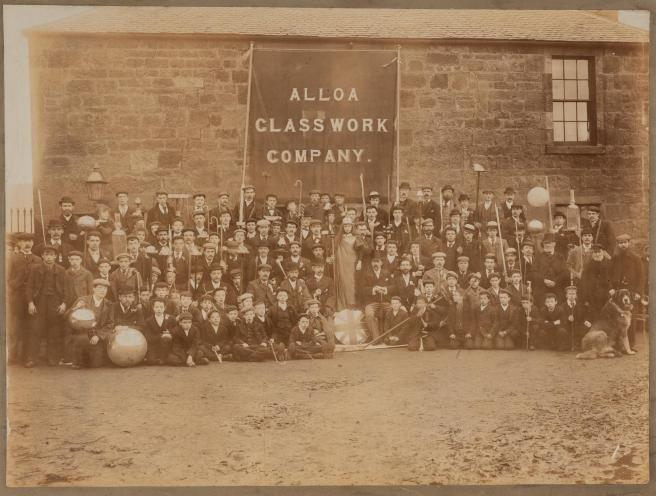Workers at Alloa glass factory pose outside the factory. Some hold blowpies, others hold glass items. Children and a dog sit at the front.