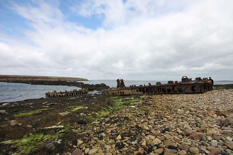 Rusted metal remains of a defence structure stretching between two islands