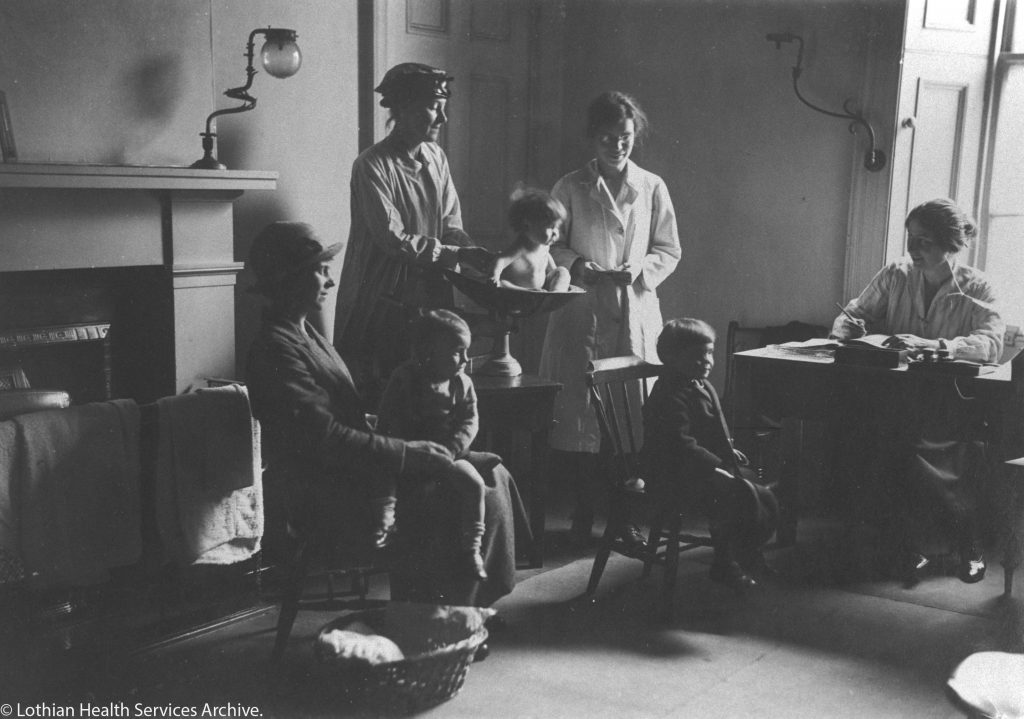 Print in an album showing mother and children with doctor and nurses in a clinic at Grove Street Dispensary, Grove Street, Edinburgh.