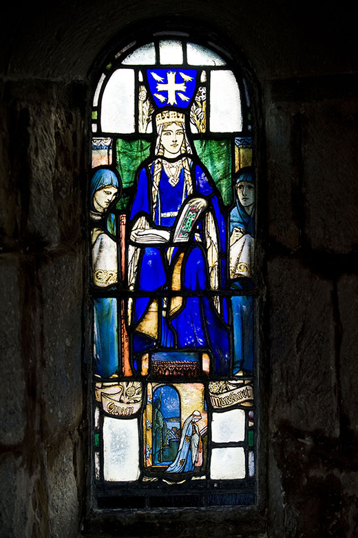 A stained glass depiction of St Margaret in St Margaret's Chapel, Edinburgh. She wears blue robes and a gold crown and has an open book , possibly a Bible, on her lap.