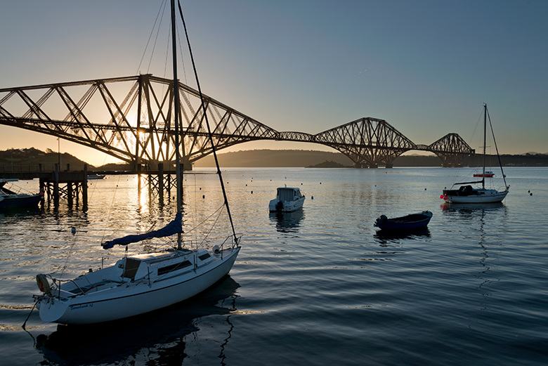 Small boats pictured in front of the iconic Forth Bridge from the shores of the Firth of Forth at North Queensferry