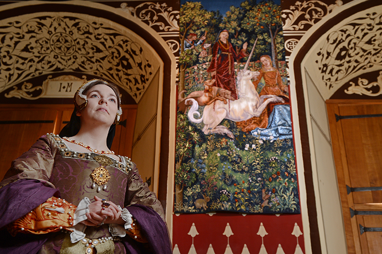 a woman dressed in renaissance clothes stands in front of the Hunt of the Unicorn tapestry, which shows the unicorn being attacked by hunting dogs