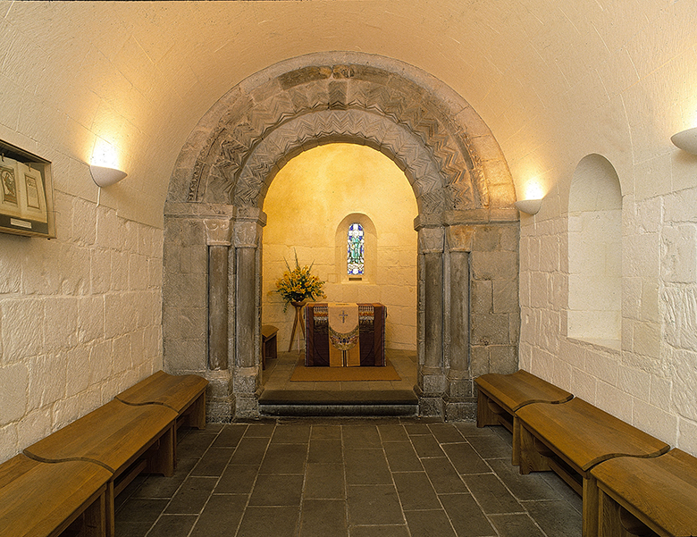 An unassuming chapel interior. Two wooden benches flank a small aisle, at the end of which an altar sits under a stone archway. A small window and a bunch of flowers can be seen behind the altar.