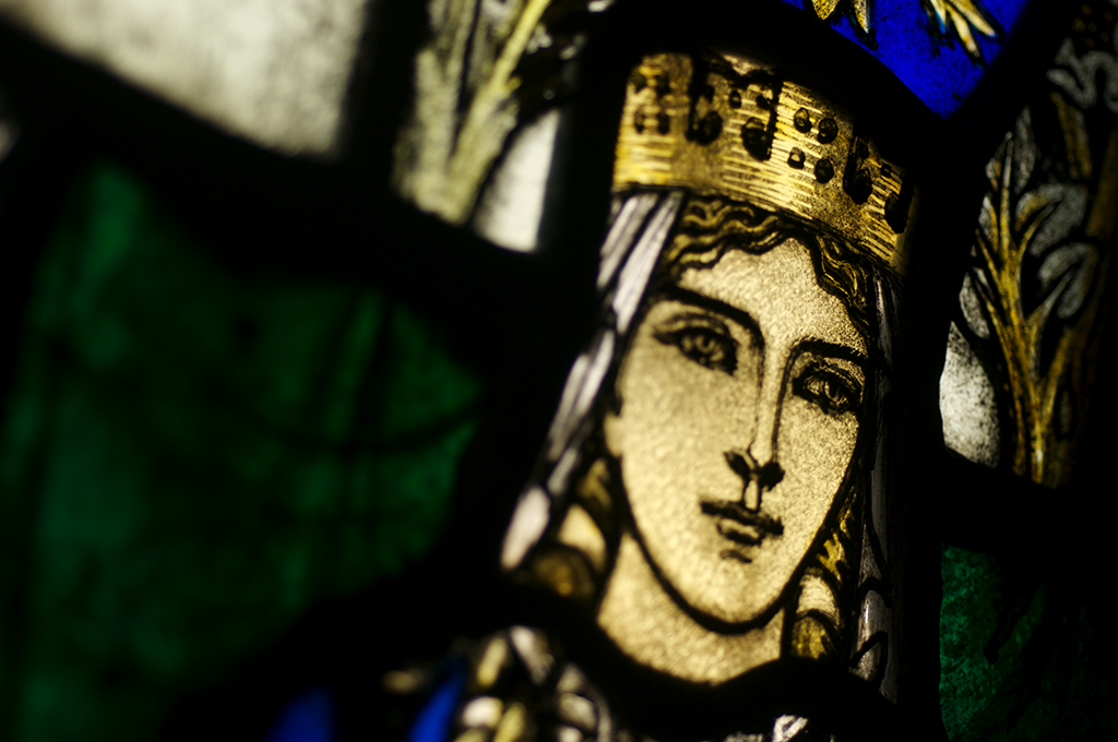 A close-up photo of a stained glass depiction of St Margaret. She has gold hair and wears a gold crown.