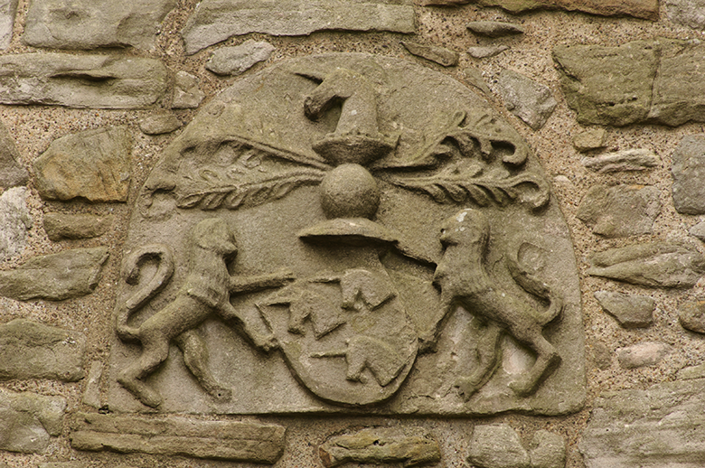 An ornate carving featuring a shield with three unicorn heads held by two lions