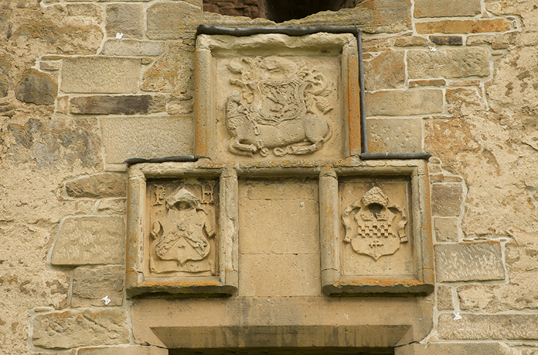 heraldic symbols carved above a doorway, including a unicorn with a shield