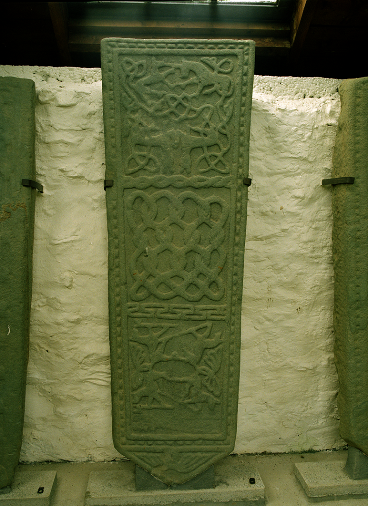 View of a grave slab which features a medieval carving of entertwined animals, including a unicorn