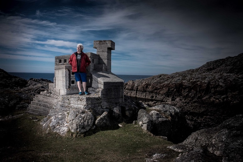 Val McDermid standing on part of a ruined castle. The sea and a dramatic cloudy sky provide the backdrop.