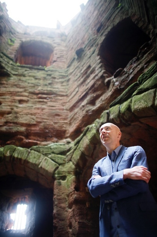Chris Brookmyre standing within the ruins of a castle, sunlight is entering through a barred window and the open roof.