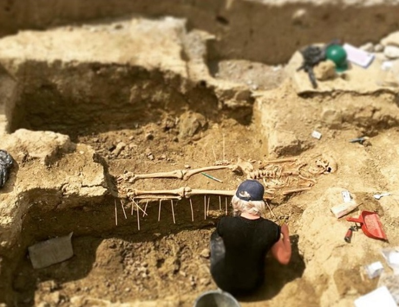 An archaeologist working on site. She is crouched beside a human skeleton which has been uncovered.