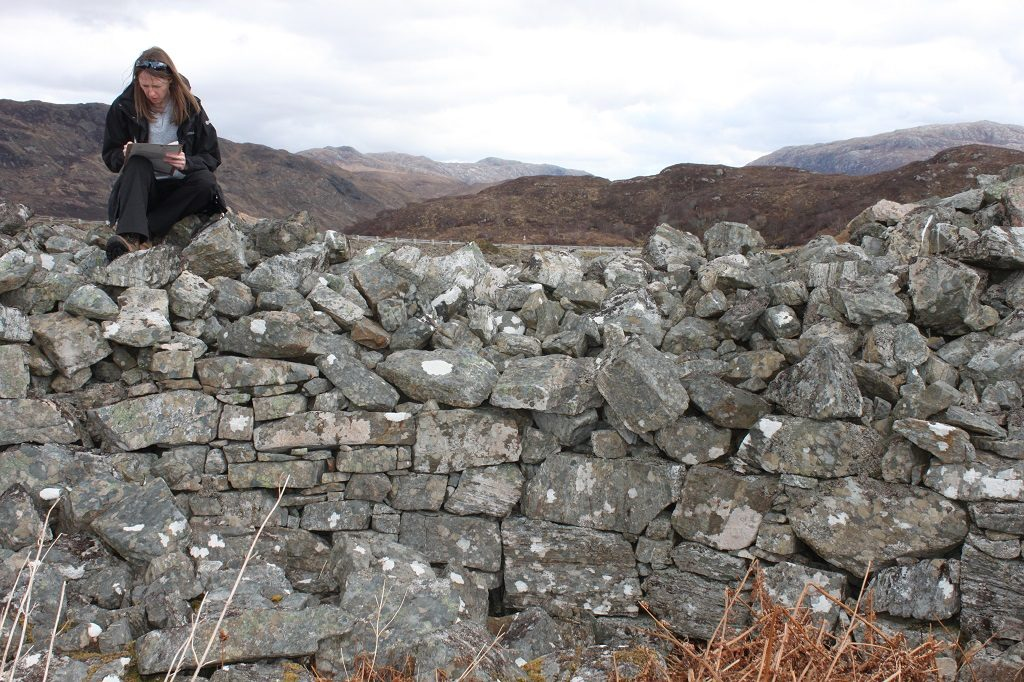 Archaeologist Kirsty Millican sits on a pile of stones while making notes on a clipboard