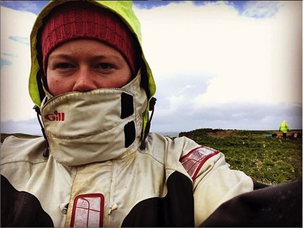 A 'selfie' of an archaeologist working on site wearing a buttoned up coat, hood and hat.