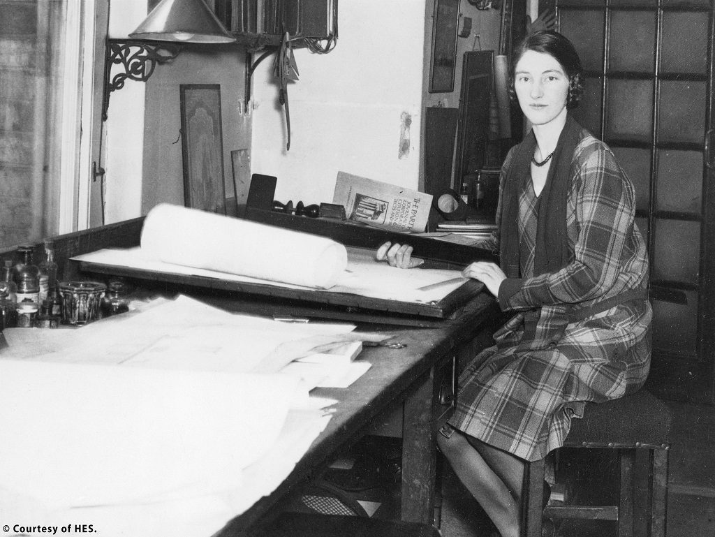 a black and white photo of Kathleen Veitch. She is a young professional woman sitting at an architects' desk