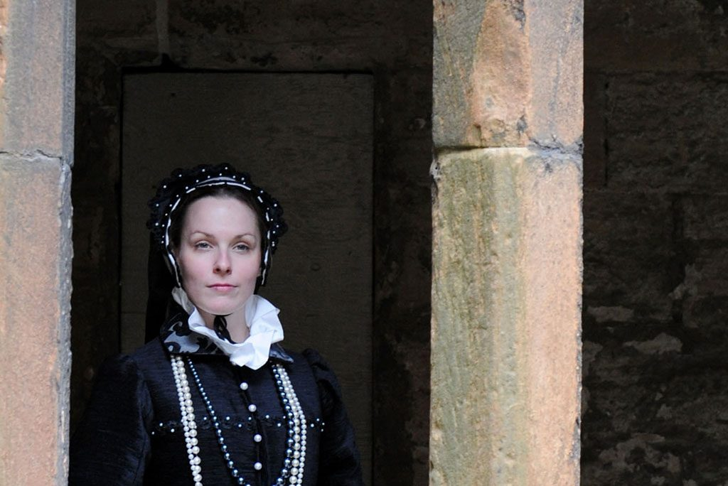 woman in renaissance costume looks through a stone archway