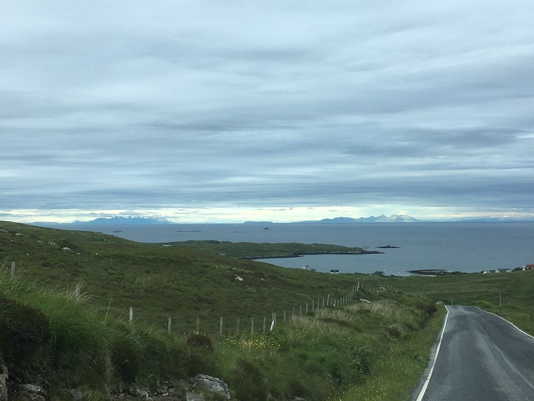 A view of distant isles taken from a remote, empty road.