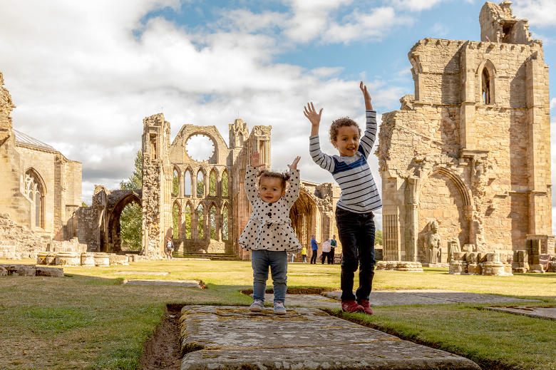 Two children make a pose in front of the ruins of a cathedral
