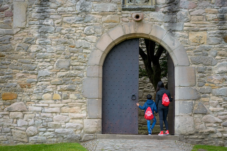 "Two young visitors opening the enormous front door of Craigmillar Castle. They are wearing red drawstring bags marked ""Explorer Pack"""