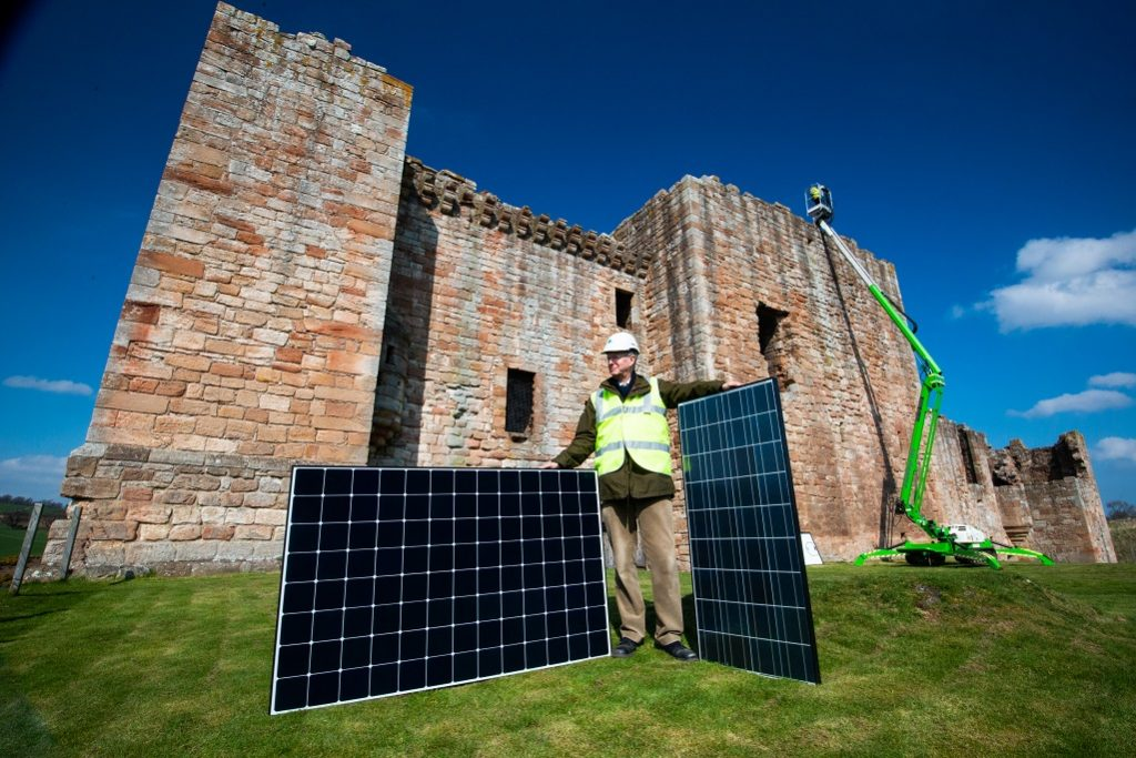 A man in a hard hat and high visibility vest stands in front of a caslt eholding two solar panels. There is a green cherry picker extending to the roof of the castle in the background.