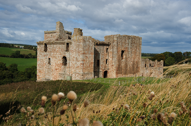exterior of Crichton Castle in a remote location with wild grass in the foreground
