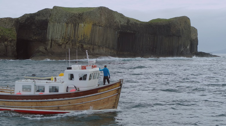 A TV presenter stands at the helm of a small boat as it passes a distinctive geological feature.