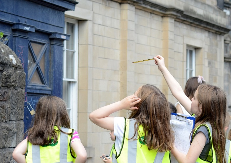 Youth club members wearing high viz jackets inspect a police call box on Canongate, Edinburgh