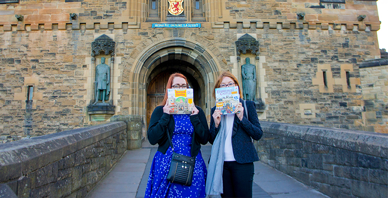 Two publishers posing in front of the entrance to Edinburgh Castle with copies of the new children's books