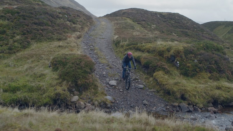 A TV presenter on a mountain bike descending a rocky track, about to ford a stream