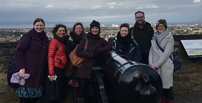 A group of seven people pose beside a large cannon on the battlements of Edinburgh Castle. The Firth of Forth can be seen in the background.