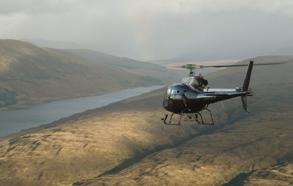 A helicopter flying towards a loch with a rainbow forming in the distance