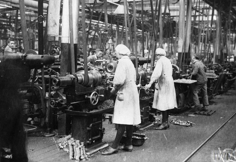 Archive photo showing women munitions workers operating machinery. They are wearing white work coats and hats.