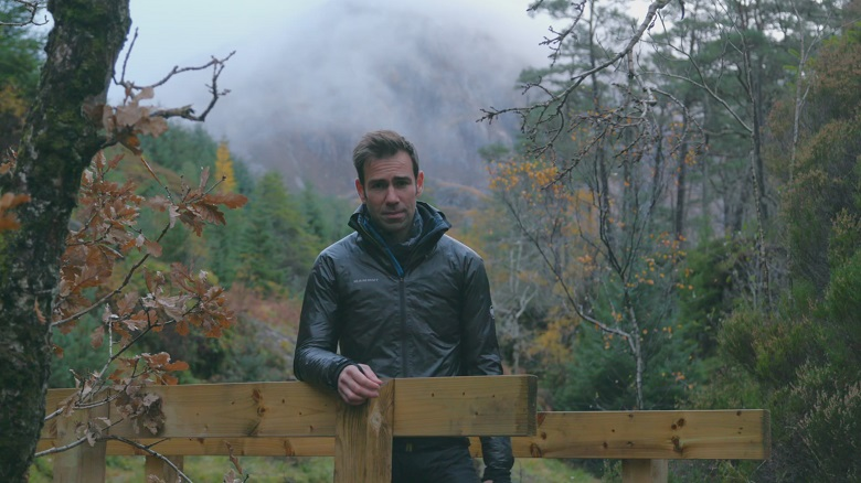 A rain-soaked TV presenter standing on a footbridge in a wet and misty forest